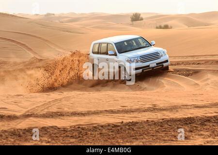 Dune bashing among the sand dunes outside Dubai, UAE. No brand logos on car or license tag numbers - Stock Photo