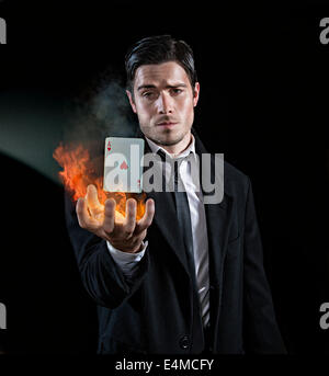 Magician produces an ace in flames - Stock Photo