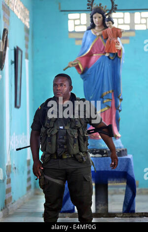 Heavily armed national policeman guarding under a statue of Virgin Mary, Mass service in a church in Choco Province, - Stock Photo