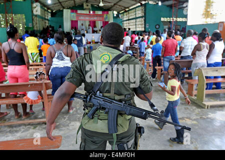 Heavily armed national policeman guarding a mass service in a church in Choco Province, Colombia - Stock Photo