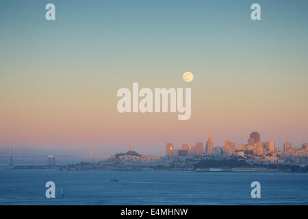 The beautiful San Francisco skyline at dusk with a full moon rising - Stock Photo