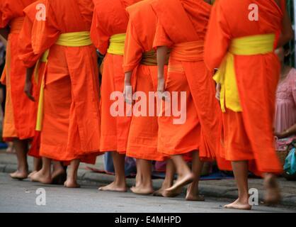 Buddhist monks in Luang Prabang, Laos make their morning ritual collecting rice - Stock Photo