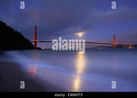 A full moon rises over San Francisco and the Golden Gate Bridge from Kirby Cove in the Marin Headlands. - Stock Photo