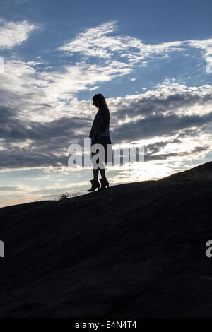 silhouette of a woman lost at sunset in a dress holding a bag with clouds in the background - Stock Photo