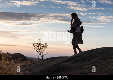 silhouette of woman on phone walking barefoot through remote hills at dusk holding shoes in hands - Stock Photo