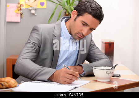 Businessman working at his breakfast bar - Stock Photo