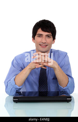 Relaxed man sitting at a desk - Stock Photo