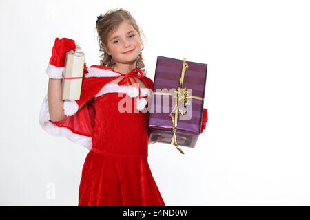Girl in a Santa costume bearing gifts - Stock Photo