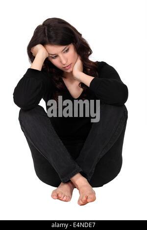 Woman with neck pain sat on floor - Stock Photo