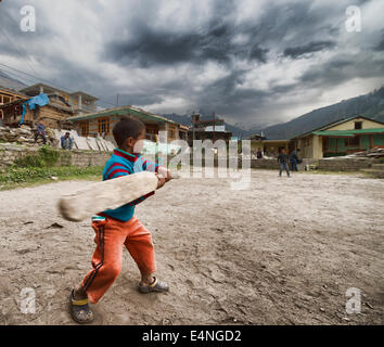Indian kids playing cricket in a village - Stock Photo