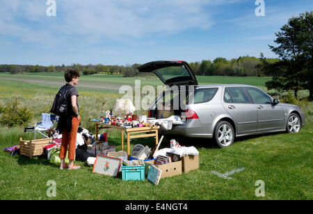 Young woman looking for bargain on car boot sale in Swedish countryside. - Stock Photo