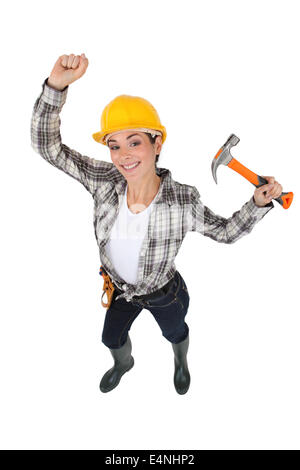 Mason jubilant women with hammer in hand - Stock Photo