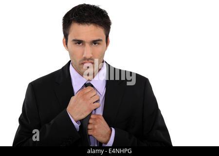 Businessman fixing his tie - Stock Photo