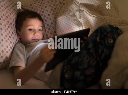 Boy (6-7) using digital tablet in bed - Stock Photo