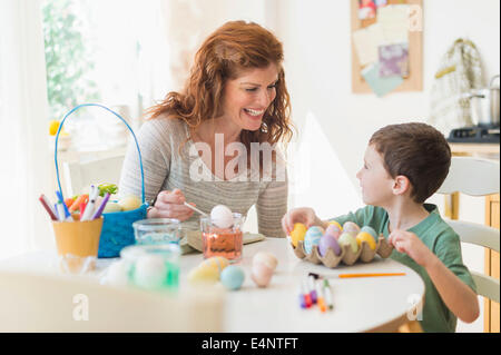 Mother and son (6-7) painting Easter eggs - Stock Photo