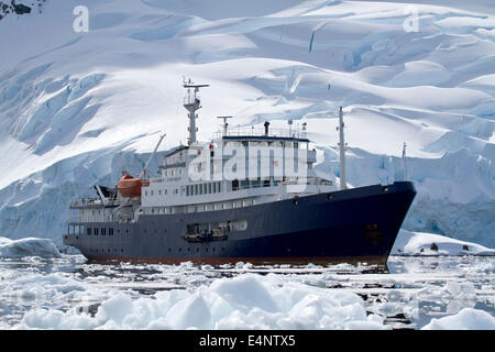 big blue tourist ship in Antarctic waters against the backdrop of glaciers - Stock Photo