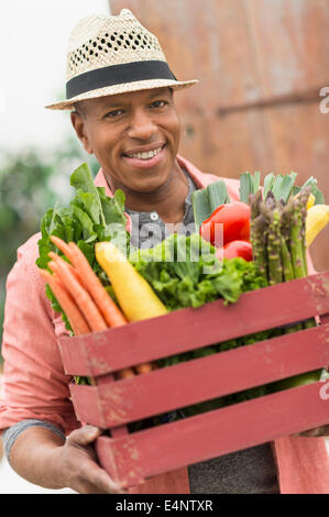 Portrait of man carrying crate full of fresh vegetables - Stock Photo