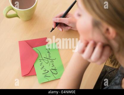 Woman writing greeting card at christmas - Stock Photo