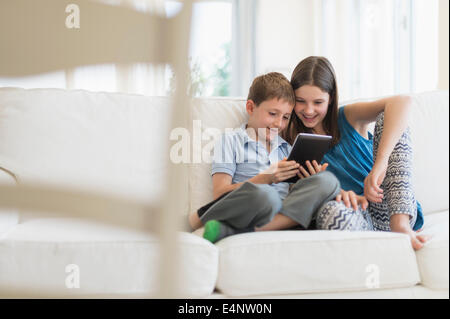 Boy and girl (8-9, 10-11) sitting on sofa using digital tablet - Stock Photo