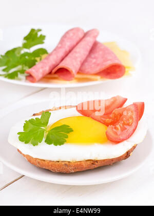 Sandwich with fried egg, tomato slices and parsley on wooden table - Stock Photo