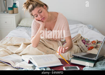 Young woman studing in bed - Stock Photo