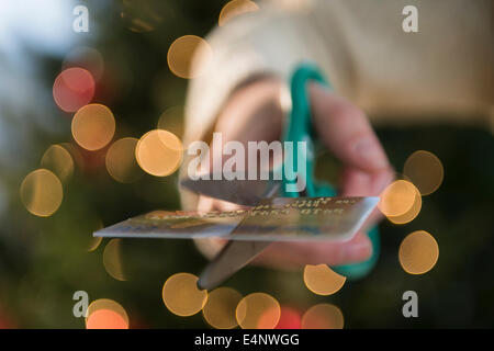 Studio Shot of female hand cutting credit card with scissors - Stock Photo