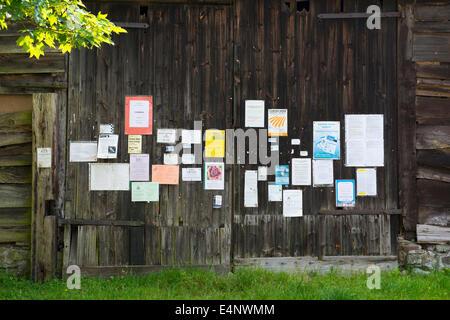 Village notice board on barn doors in Hopesay, Shropshire, England. - Stock Photo