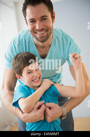 Father embracing son (8-9), Boy flexing muscles - Stock Photo