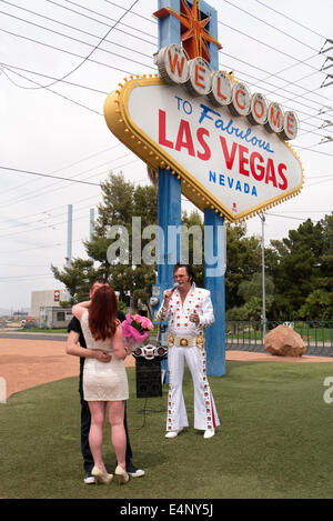Wedding at the Las Vegas sign with Elvis impersonator. - Stock Photo