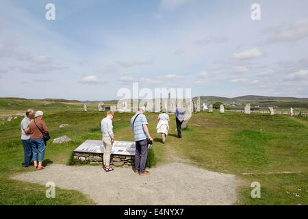 Tourists reading the information board for Callanish Stone Circle. Calanais Isle of Lewis Outer Hebrides Western - Stock Photo