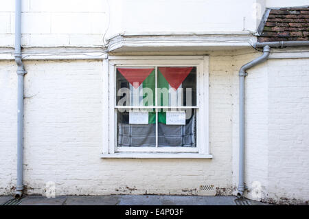 Flag of Palestine hanging in UK window with hand written notice in English and Arabic saying 'stand with Gaza' - Stock Photo
