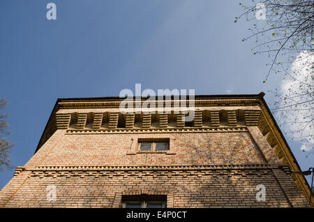 red brick manor architectural fragment with small windows and ornaments on blue sky background - Stock Photo