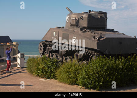 Boy taking photo of French 2nd DB Sherman tank Berry Au Bac on display at Arromanches, Normandy, France in July - Stock Photo