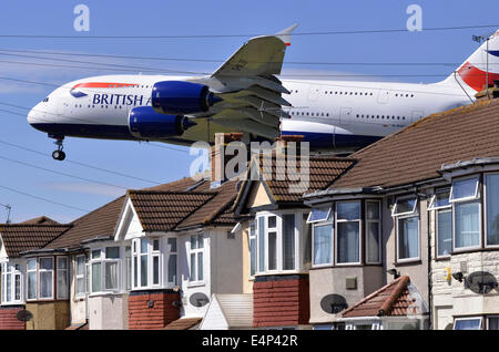 Heathrow runway approach by Airbus A380 British Airways plane low over houses on landing approach for London Heathrow - Stock Photo