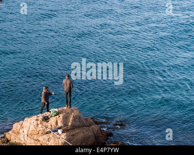 Shore Fishing off the rocks. Two men fish from a rock just below the castle near the shore at Tossa de Mar. - Stock Photo