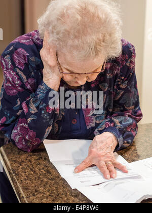 Trying to Understand a Letter. A senior woman reads a letter with her head held up by one hand while her other marks - Stock Photo