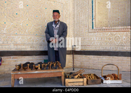 Local man with bread stamps in front of the Kalon Mosque, Bukhara, Uzbekistan - Stock Photo