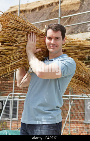 Thatcher Carrying Bundles Of Reeds Working On Roof - Stock Photo