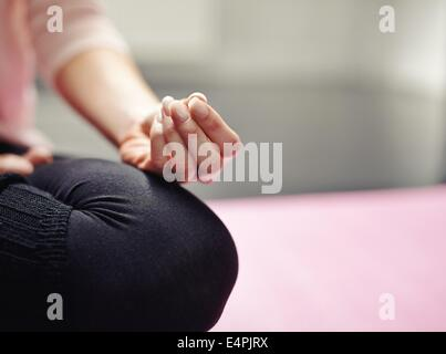 Low section of woman sitting cross-legged on mat meditating in yoga posture. Cropped image of woman practicing yoga - Stock Photo