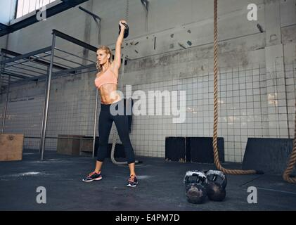 Young fitness woman lifting a heavy weight kettle bell at gym. Caucasian female athlete working out at gym. Fit - Stock Photo