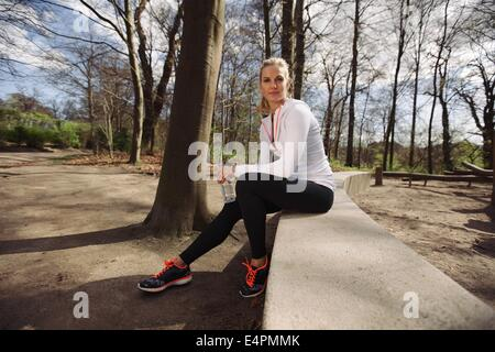 Female runner taking a rest from training in nature. Attractive young woman sitting relaxed with a water bottle. - Stock Photo