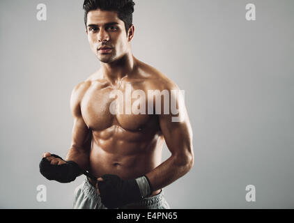 Portrait of fitness male model wearing sports gloves posing on grey background. Muscular young man looking fit after - Stock Photo