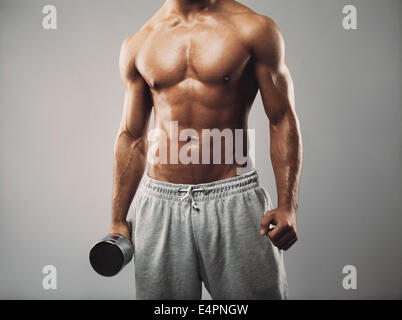 Studio shot of a male model in sweatpants holding dumbbell on grey background. Shirtless muscular man working out. - Stock Photo