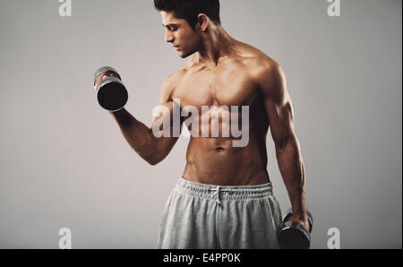 Hispanic young muscular man doing heavy dumbbell exercise for biceps. Fitness male model working out with dumbbells - Stock Photo
