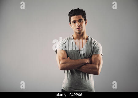 Portrait of young muscular man posing against grey background. Handsome young hispanic male model standing with - Stock Photo