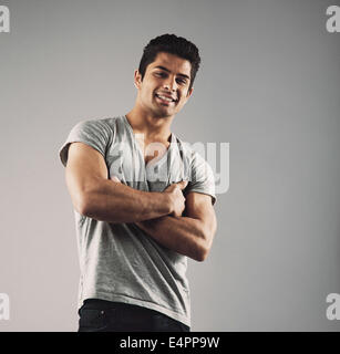 Portrait of smart young muscular man posing against grey background. Happy young hispanic male model standing with - Stock Photo