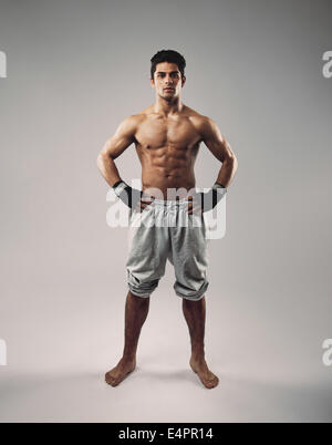 Portrait of shirtless muscular man posing in sweatpants. Strong young guy standing on grey background. - Stock Photo