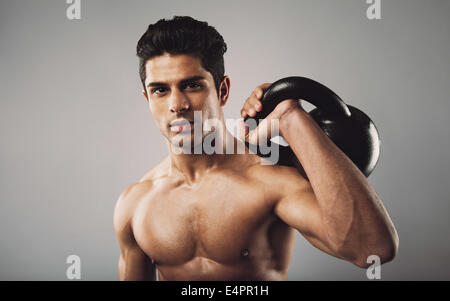 Portrait of hispanic fitness male model holding kettle bell on grey background. Shirtless young doing crossfit work - Stock Photo