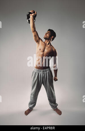 Handsome and athletic young man lifting a kettlebell with one hand as a crossfit workout. Muscular man doing one - Stock Photo