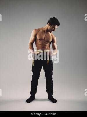 Full length image of fit young man with tape measure around his waist measuring his body. Masculine young hispanic - Stock Photo